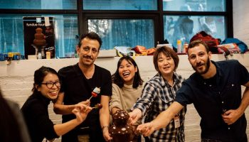 Smiling people holding fruit skewers over a chocolate fountain at the 192 Spadina housewarming party