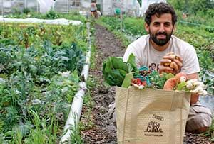 Ran G., Founder and CEO of Fresh City Farms, poses with a bag of fresh produce from the farm.