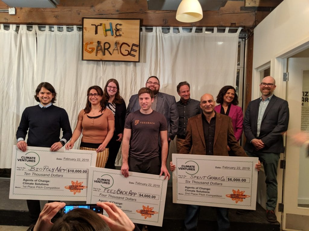 Group photo of Agents of Change Pitch Night winners on stage, holding large cheques