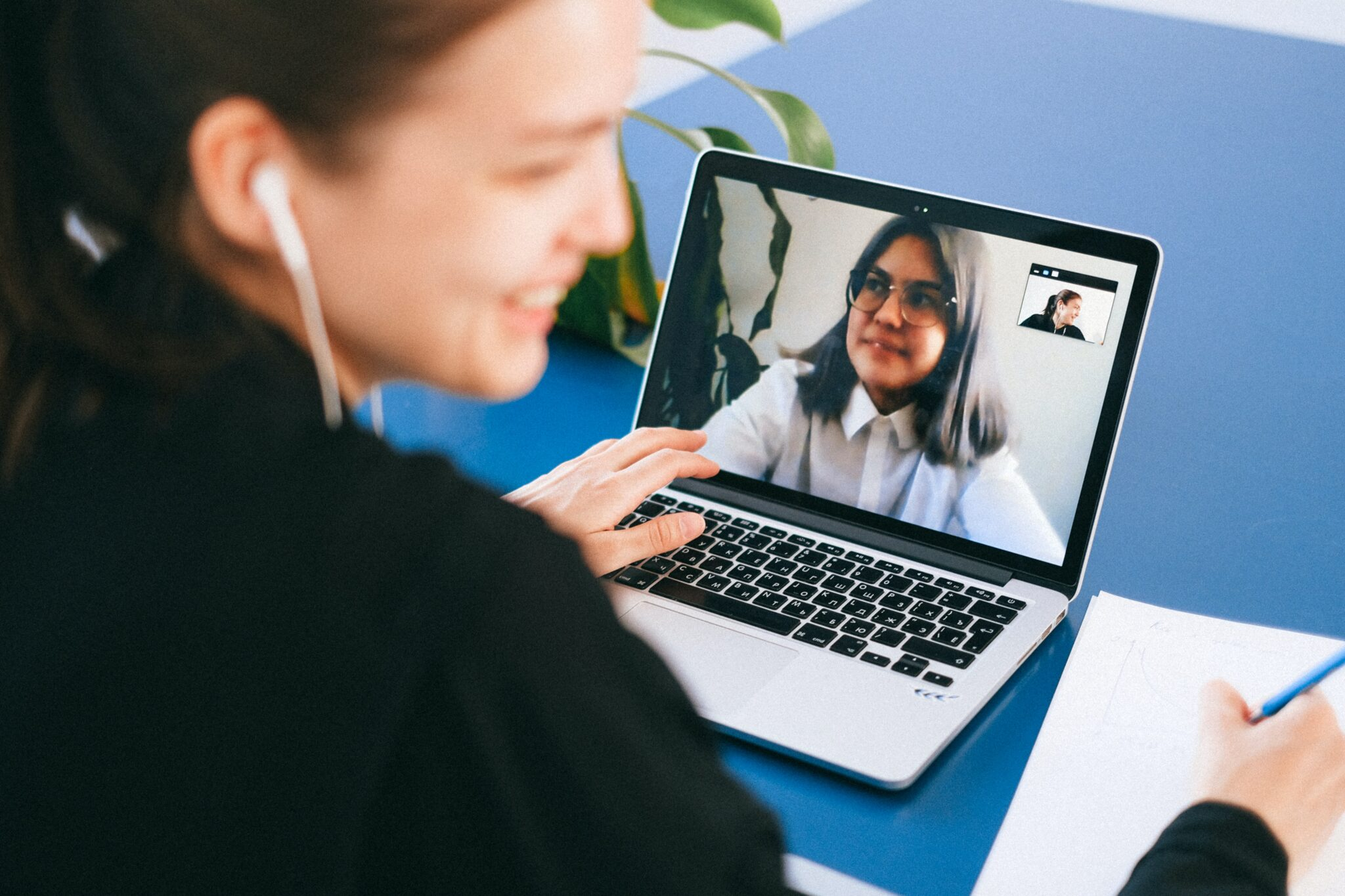 A woman smiling as she sits at her laptop.