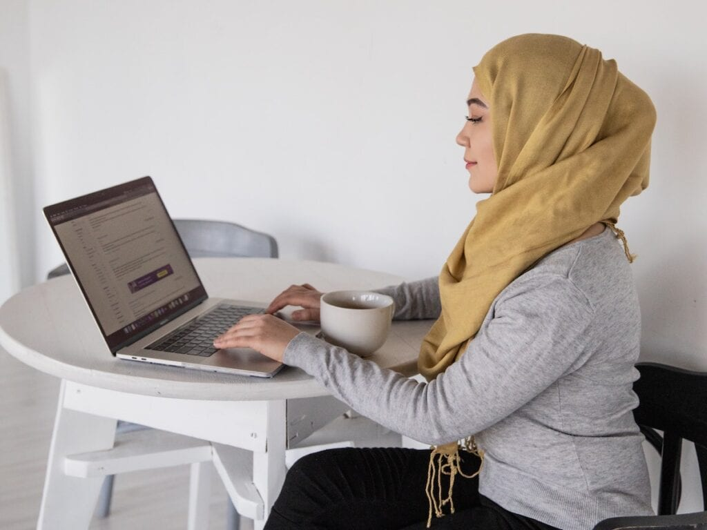 Person in yellow hijab and grey long-sleeved shirt sitting at a round table using a laptop.