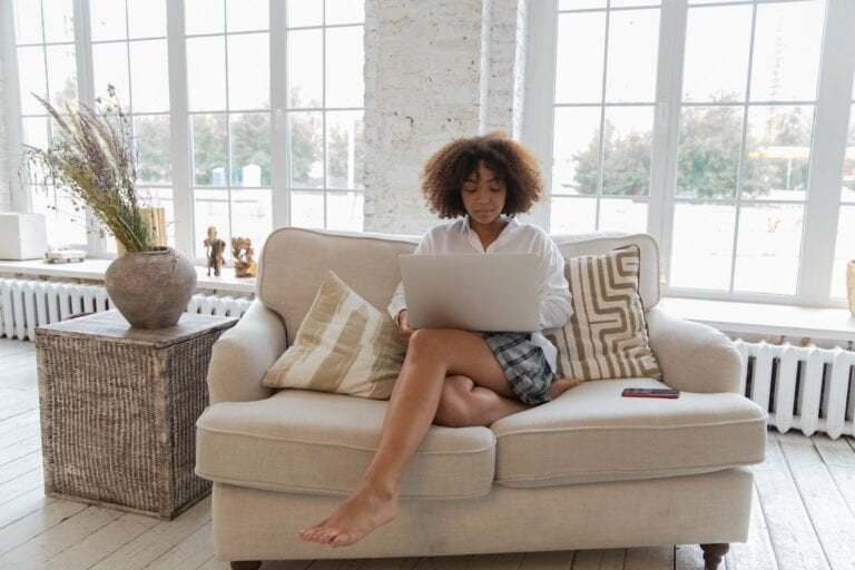 Woman sitting cross-legged on beige couch in loungewear. Couch is in front of bright floor-to-ceiling windows.