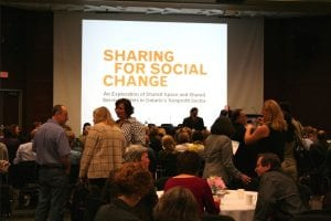 """Audience looking up at a slide that reads """"Sharing for Social Change"""""""
