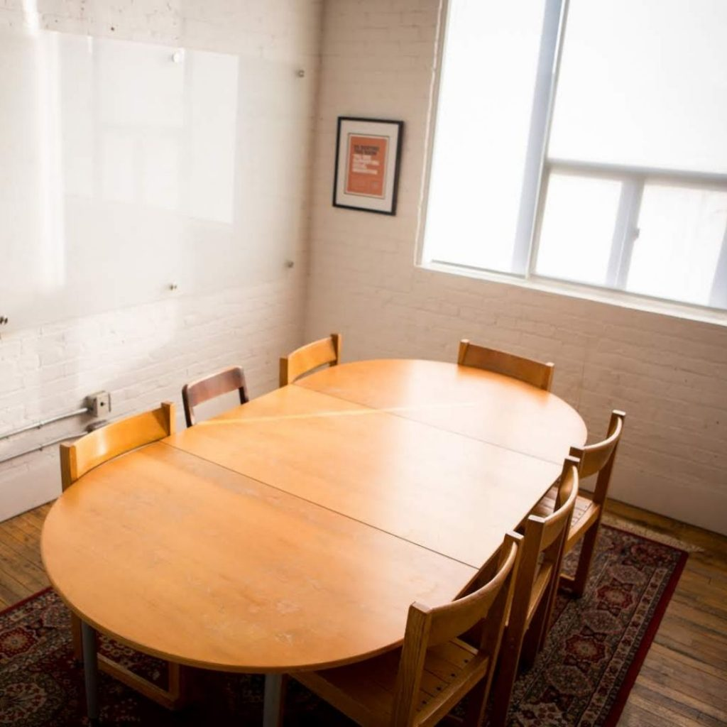 Meeting room in CSI Annex. Seven chairs are arranged around a wooden table. On one wall, a whiteboard. On another, large windows with lots of natural light.