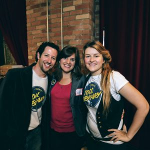 Three people (two in Toronto Tool Library teeshirts) smiling at the 2012 launch event of the Catapult Loan program
